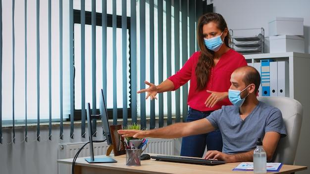 Arbeiter, die während des coronavirus im büroraum mit schutzmasken sprechen. team in einem neuen normalen büroarbeitsplatz in einem persönlichen unternehmensunternehmen, das auf der computertastatur tippt und auf den desktop zeigt