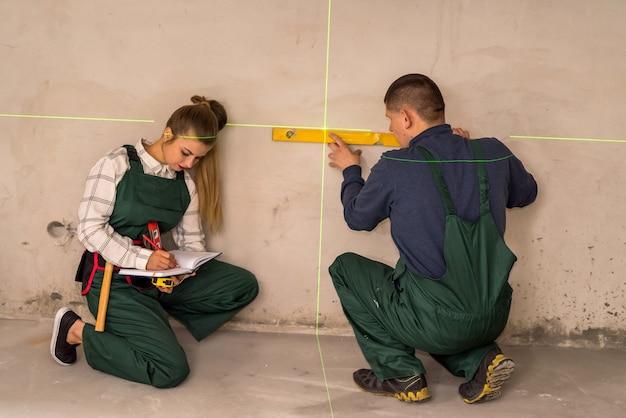 Arbeiter, die wände mit laser-nivelliergerät überprüfen