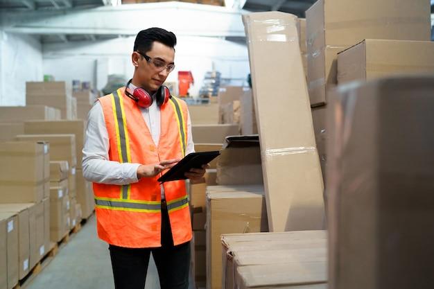 Arbeiter eines logistiklagers mit einer tablette