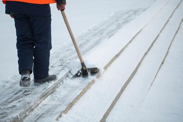 Arbeiter fegen im winter schnee von der straße, reinigen die straße vom schneesturm.