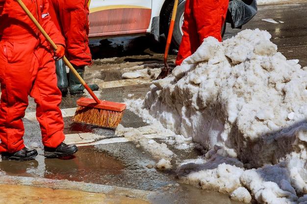 Arbeiter fegen schnee von der straße im winter.