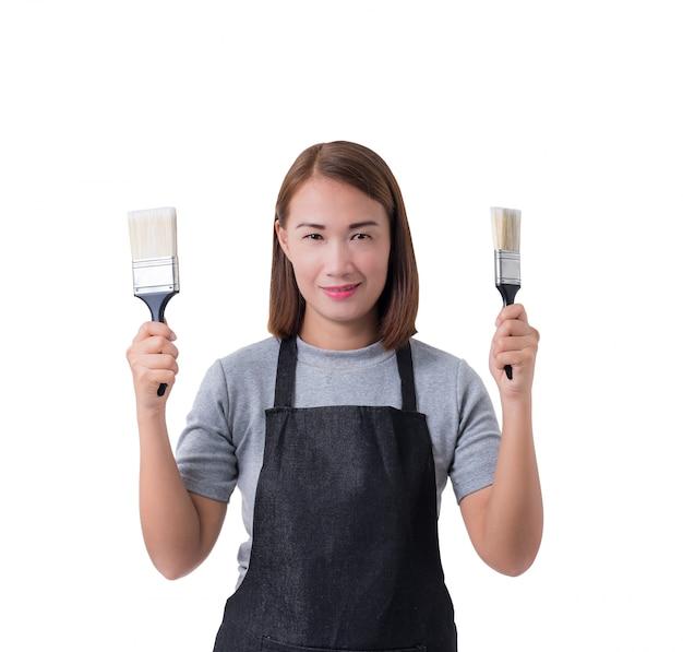 Arbeiter frau oder service frau im grauen hemd und schutzblech hält pinsel