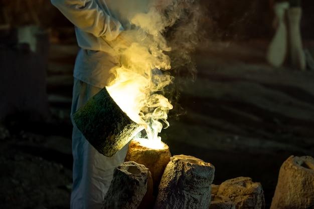 Arbeiter gießen gold in die form