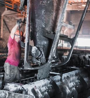 Arbeiter gießen nassen zement in die formen. herstellung von betonplatten