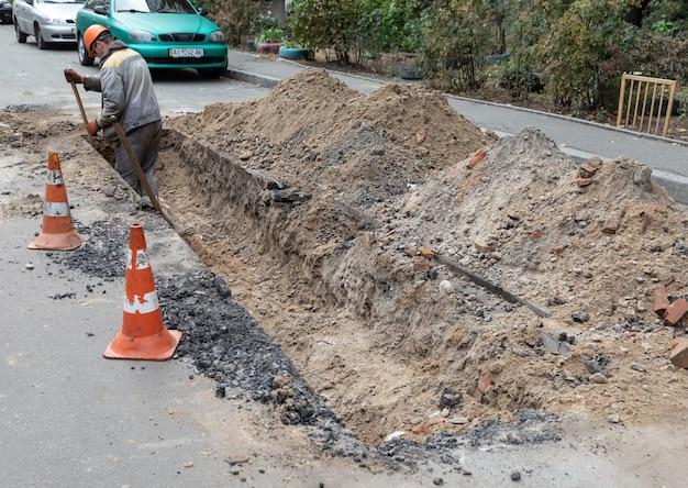 Arbeiter gräbt einen graben auf einer stadtstraße