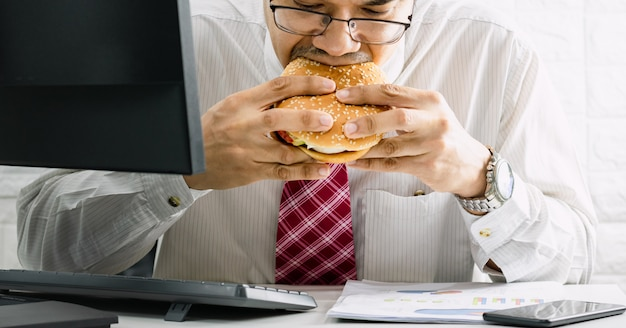 Arbeiter haben keine zeit, dringend junk-food-hamburger zu essen, während sie im büro arbeiten