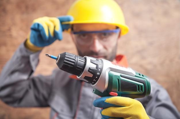 Arbeiter hält akku-schraubendreher. bauwerkzeug