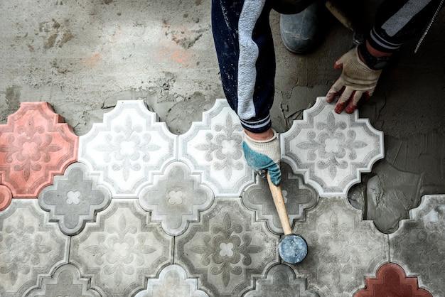 Arbeiter hält eine betonpflasterfliese. das konzept der arbeit an der verlegung figürlicher dekorativer pflastersteine.
