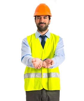 Arbeiter hält etwas über weißem hintergrund