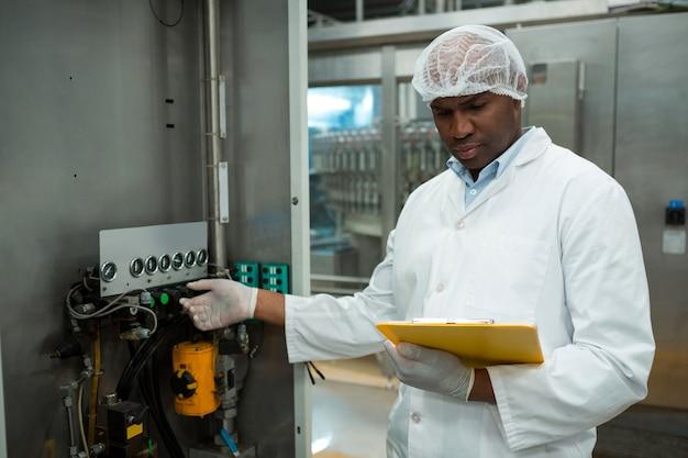 Arbeiter hält zwischenablage während des betriebs der maschine in der saftfabrik