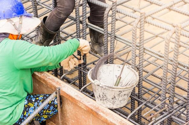 Arbeiter hände mit stahldraht und zangen, um bewehrung zu sichern, bevor beton darüber gießt