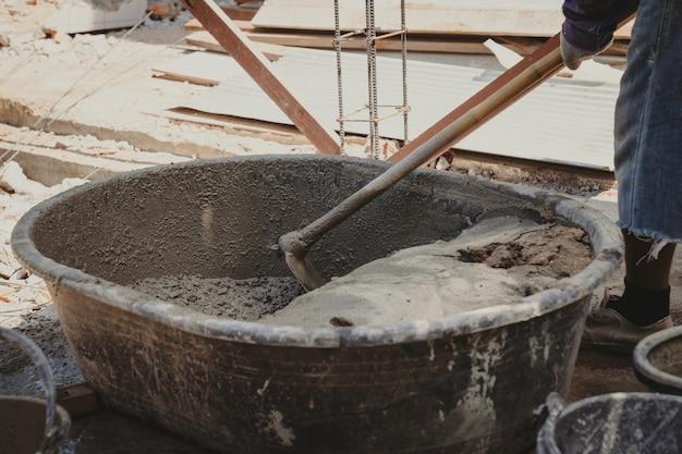 Arbeiter hausbauer mischen mörtel aus einem trog im eimer