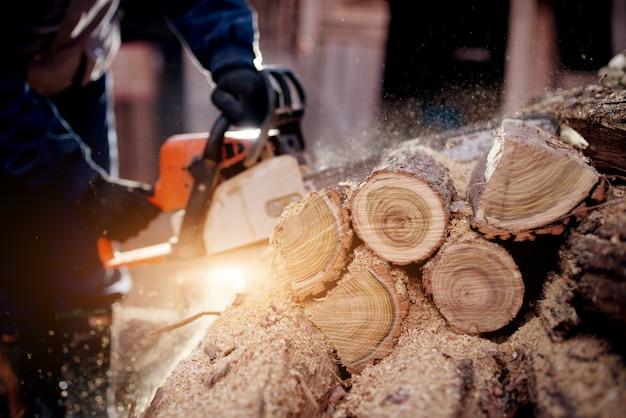Arbeiter holzfäller eine kettensäge, die ein holz sägt.