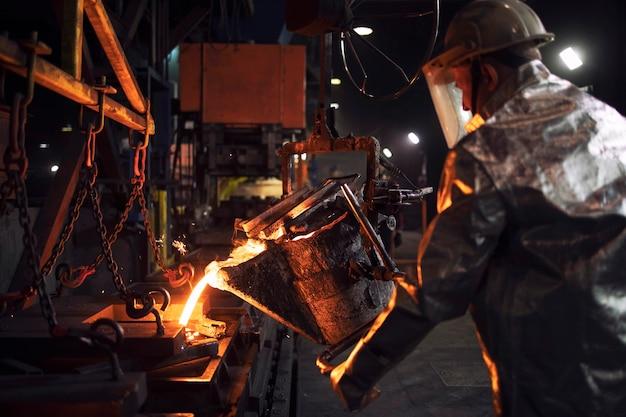 Arbeiter im aluminisierten schutzanzug gießen geschmolzenen stahl in die gießerei.