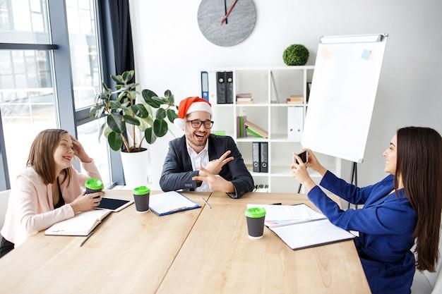 Arbeiter im büro. freundliche attraktive leute, die neues jahr oder weihnachten feiern. brunette, der foto des mannes und des lächelns macht. glücklich zusammen. ferien bei der arbeit.