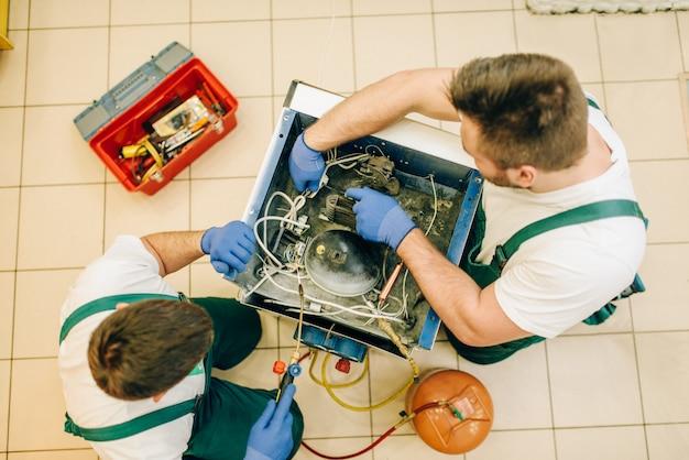 Arbeiter im einheitlichen befestigungsproblem mit kühlschrank zu hause. reparatur der kühlschrankbelegung, professioneller service