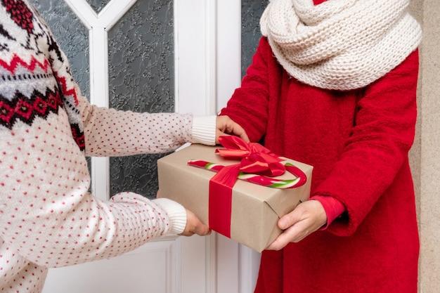 Arbeiter im roten mantel, der geschenkboxen nahe der weißen tür am vorabend der weihnachtsfeiertage liefert