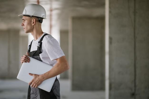Arbeiter im schutzhelm, der am laptop arbeitet
