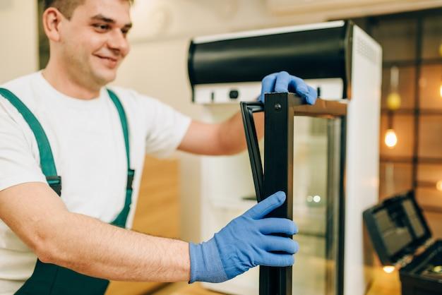 Arbeiter im uniformreparaturkühlschrank zu hause. reparatur der kühlschrankbelegung, professioneller service