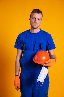 Arbeiter in bauoveralls und handschuhen auf gelbem grund hält einen schutzhelm und eine medizinische maske in der hand. das konzept der wirtschaftskrise, arbeitslosenproduktion, coronavirus