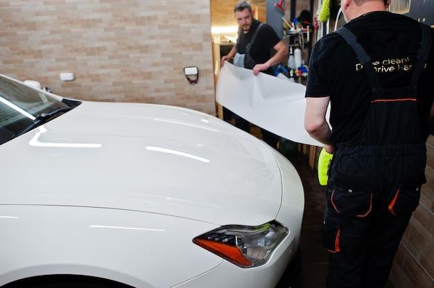 Arbeiter in der detaillierung der garage legte eine polyurethan-anti-kies-filmabdeckung in ein weißes luxusauto