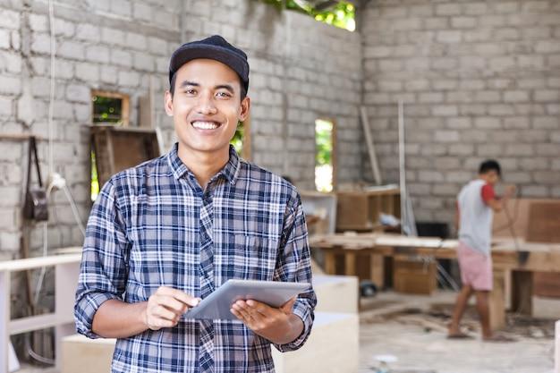 Arbeiter in der möbelfabrik arbeitet an seinem pc-tablet