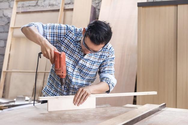 Arbeiter in der schreinerwerkstatt, die schrauben mit einem schraubendreher anbringt