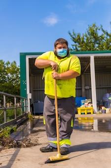 Arbeiter in einer recyclingfabrik oder reinigungsstelle und müll mit gesichtsmaske und sicherheitsschutz. porträtarbeiter mit einem besen