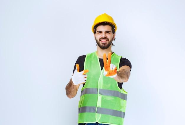 Arbeiter in gelbem helm und werkstatthandschuhen, die frieden und freundschaft senden.