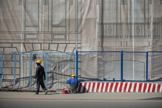 Arbeiter in gelben helmen um den zaun bemalten die grenze mit einer hellen farbe.