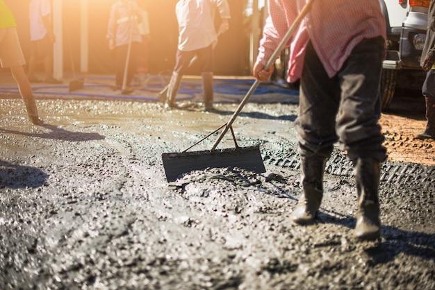 Arbeiter in gummistiefeln steht in ordentlichem zement und nivelliert die oberfläche