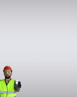 Arbeiter in helm und schutzkleidung mit einer glühbirne in den händen auf grauem hintergrund