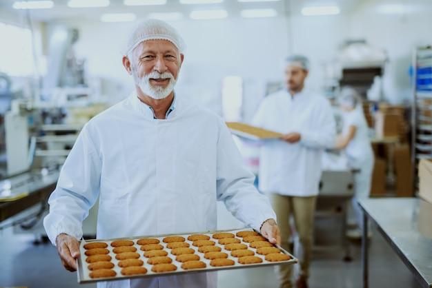 Arbeiter in lebensmittelfabriken in sterilen uniformen, die tabletts mit keksen tragen. selektiver fokus auf ältere erwachsene arbeitnehmer.