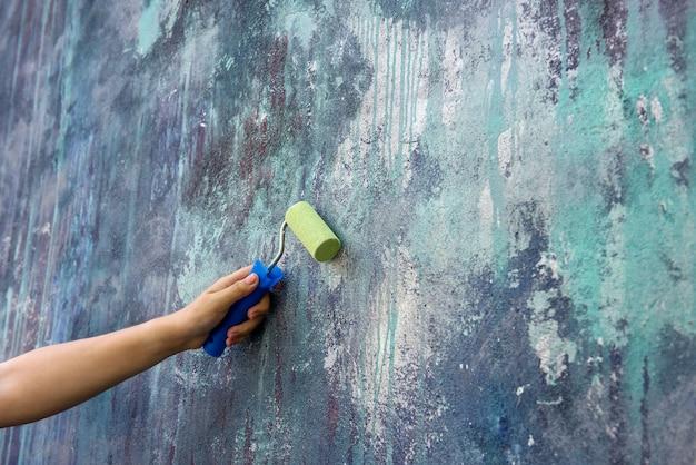 Arbeiter in overall, der wand mit rolle in der grünen farbe nahaufnahme malt
