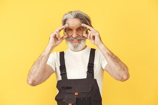 Arbeiter in overalls. mann mit werkzeugen. senior in gelber brille.