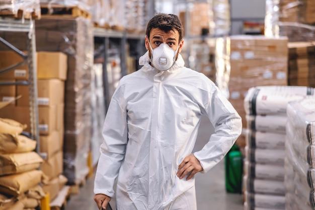 Arbeiter in schützender weißer uniform mit gesichtsmaske beim stehen im lager mit hand auf hüfte