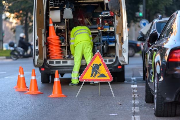 Arbeiter in seinem mit werkzeugen beladenen lieferwagen, mit zapfen vor verkehr geschützt