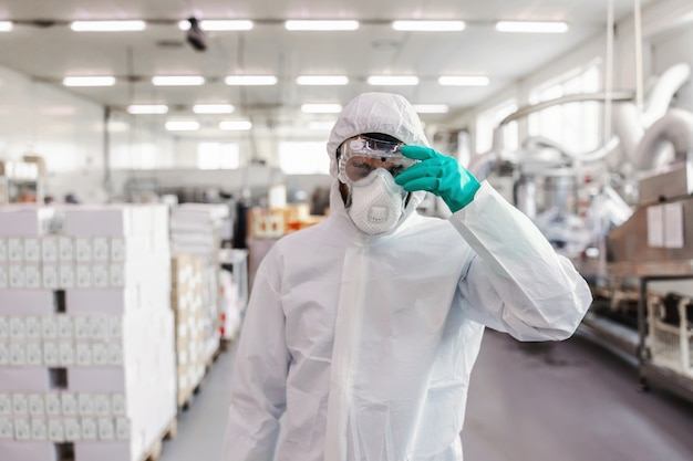 Arbeiter in steriler uniform mit gummihandschuhen, die das spritzgerät halten