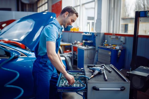 Arbeiter in uniform am werkzeugkasten, autotankstelle.