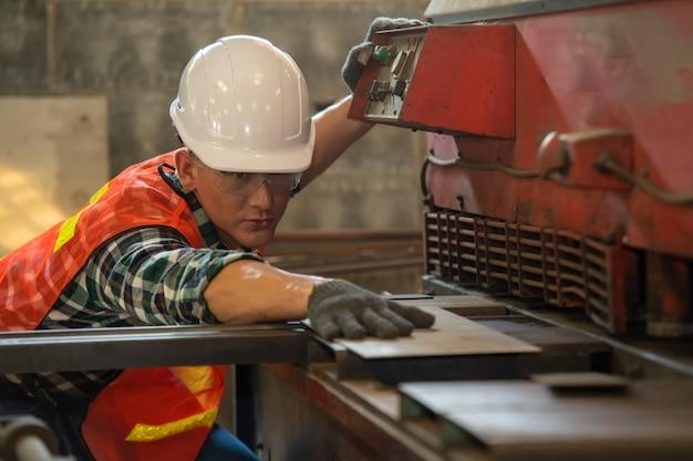 Arbeiter in uniform, der in der manuellen drehmaschine in der metallindustriefabrik arbeitet