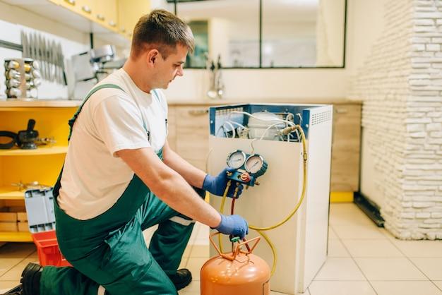 Arbeiter in uniform füllt kompressor des kühlschranks