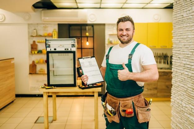 Arbeiter in uniform hält checkliste gegen kühlschrank zu hause.