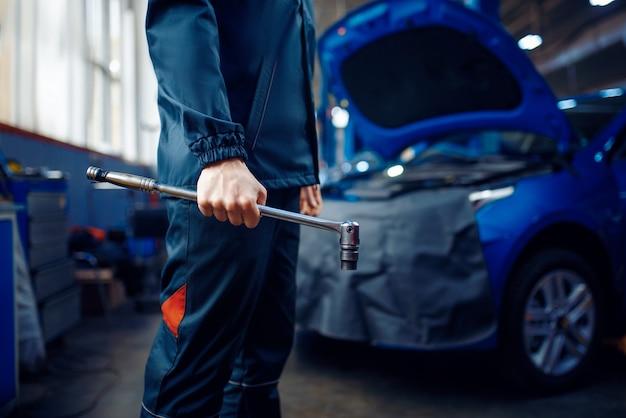 Arbeiter in uniform hält schraubenschlüssel, fahrzeug mit geöffneter motorhaube auf hintergrund, autotankstelle. überprüfung und inspektion von kraftfahrzeugen, professionelle diagnose und reparatur
