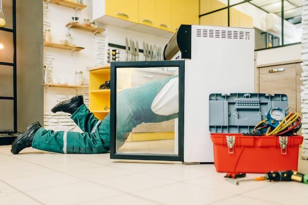 Arbeiter in uniform kletterten in den kühlschrank