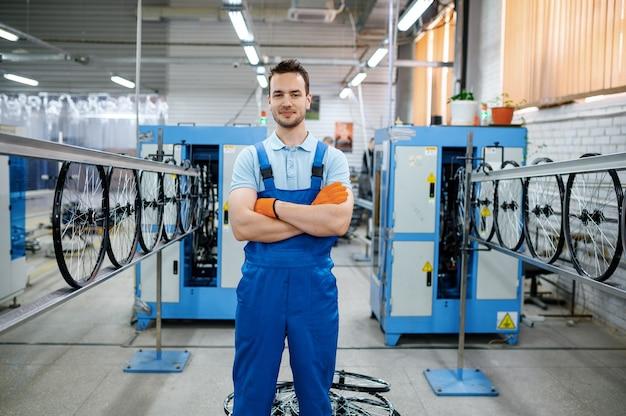Arbeiter in uniform posiert auf fahrradradfabrik. montagelinie für fahrradfelgen und speichen in der werkstatt, installation von fahrradteilen, moderne technologie