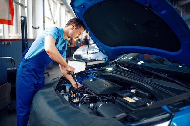 Arbeiter in uniform überprüft fahrzeugmotor, autotankstelle. überprüfung und inspektion von kraftfahrzeugen, professionelle diagnose und reparatur