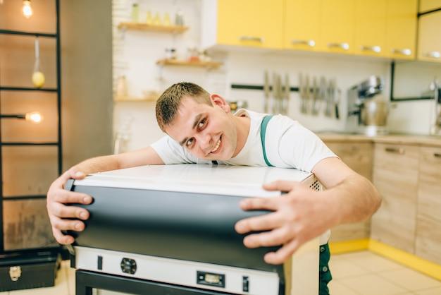 Arbeiter in uniform umarmt kühlschrank zu hause