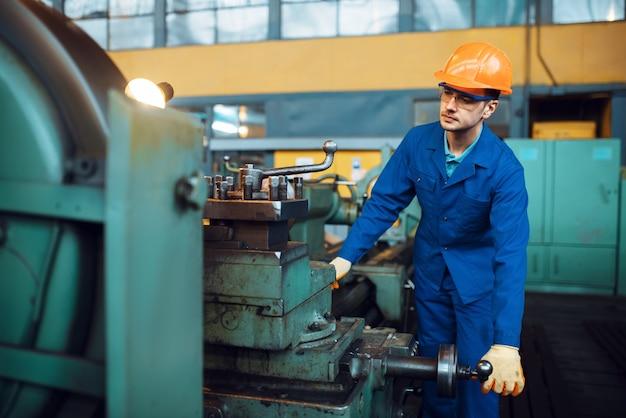 Arbeiter in uniform und helm arbeitet an drehbank, fabrik. industrielle fertigung, metallbau, fertigung