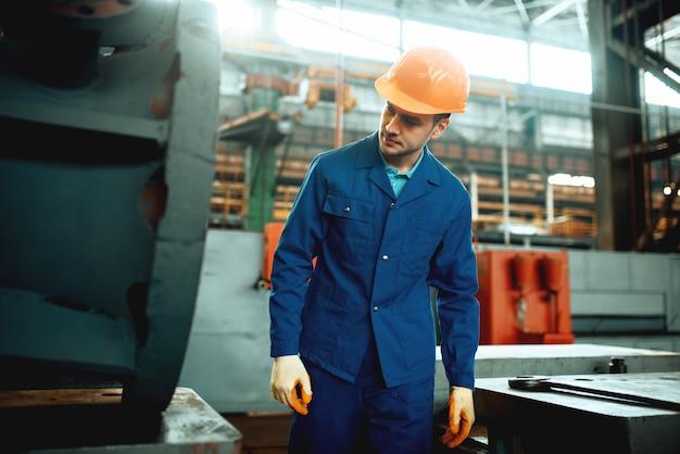 Arbeiter in uniform und helm in der metelworking-fabrik. industrielle produktion, metalltechnik, herstellung von kraftmaschinen