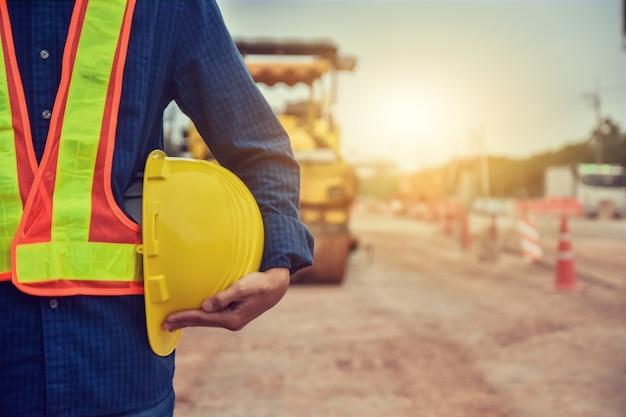 Arbeiter ingenieur, der schutzhelm hält, der auf baustellenkonstruktion steht